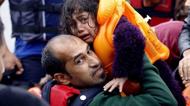 Ein Vater hebt seine Tochter vom Boot.