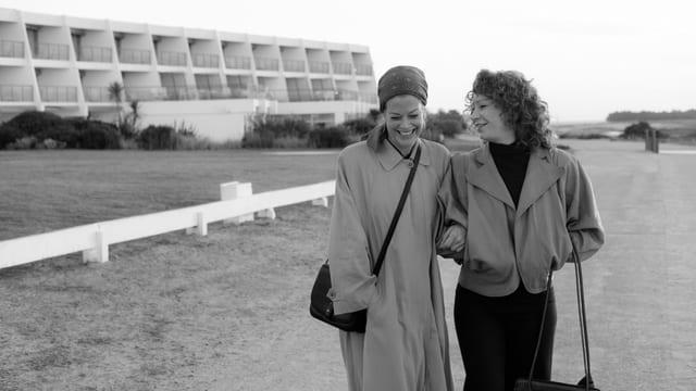 Zei Frauen spazieren am Strand, links ein Häuserkomplex. Die beiden lächeln.