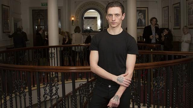 Junger Mann steht schwarz gekleidet in einem Palast-ähnlichen Gebäude