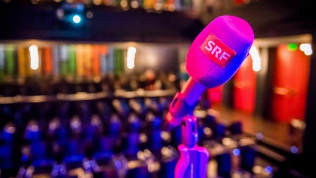 """Mikrofon mit der Aufschrift """"SRF"""" auf einer Bühne"""