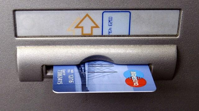 Maestro-Karte in einem Bankomatenschlitz.