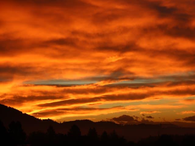 Bewölkter Himmel, die Wolken leuchten orange, gelb und rot.