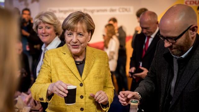 Merkel verteilt Kaffee.
