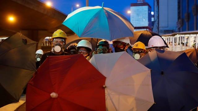 Demonstranten schützen sich mit Regenschirmen.
