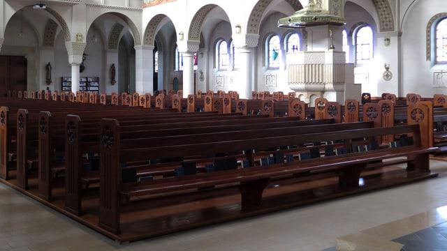 Das Innere einer Kirche mit zahlreichen dunkelbraunen Kirchenbänken.