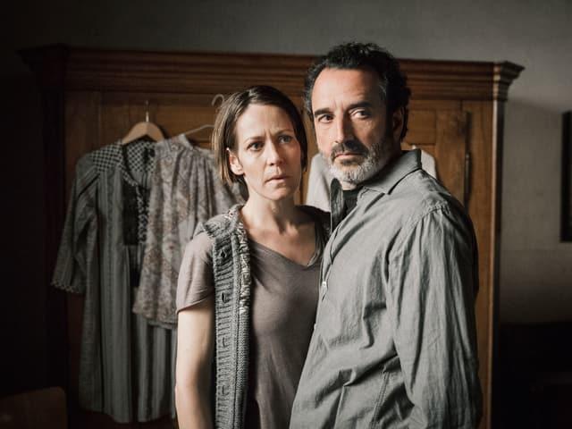 Ein Paar steht Arm in Arm vor einem Kleiderschrank.