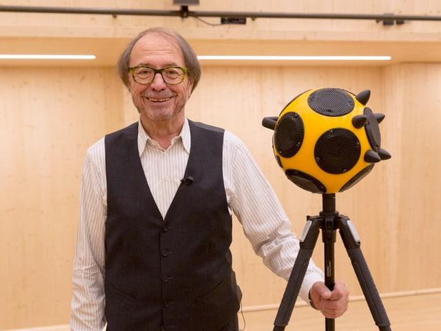 Ein älterer Herr mit Veston steht neben einem kugelrunden Akustik-Messgerät auf einem Stativ.