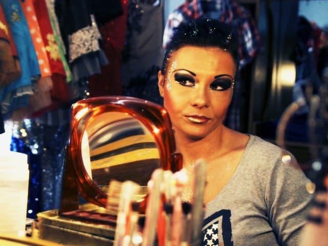Stark geschminkte Frau in einer Garderobe mit Handspiegel.
