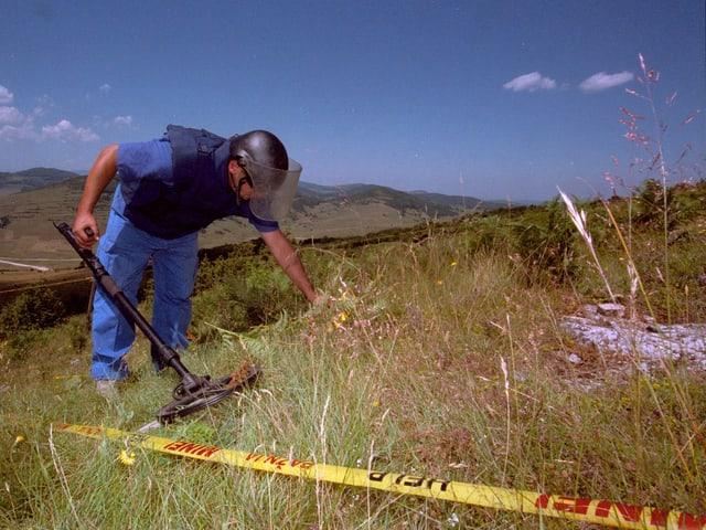 Ein Mann im Schutzanzug sucht Minen auf einem Feld in Bosnien.