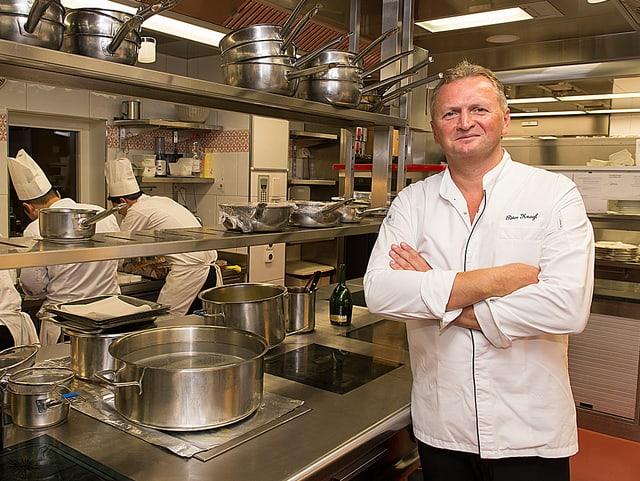 Peter Knogl posiert in der Hotelküche, im Hintergrund sind drei Köche bei der Arbeit.