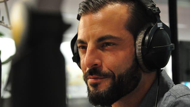Bligg, in um cun barba avant il microfon en il studio da RTR