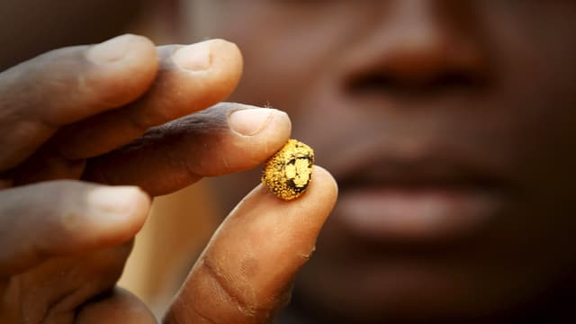 Ein Minenarbeiter hält ein Goldnugget in die Kamera.