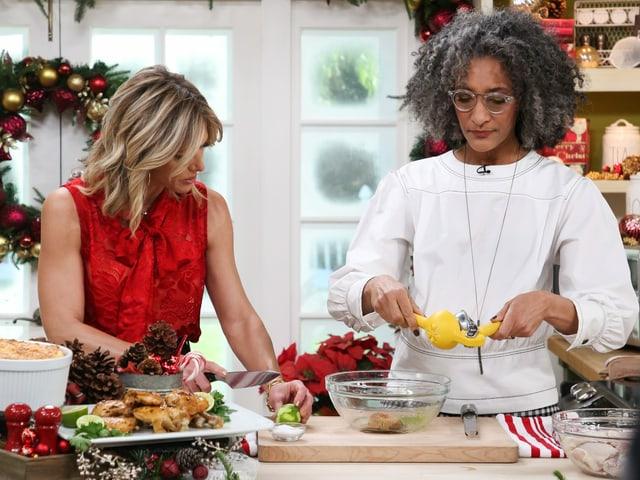 Zwei Frauen (eine Weisse und eine Schwarze) stehen da und kochen.