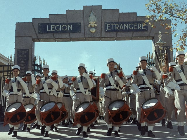 """Farbfoto einer Militärparade vor einem Tor mit der Aufschrift """"Legion etrangere"""""""