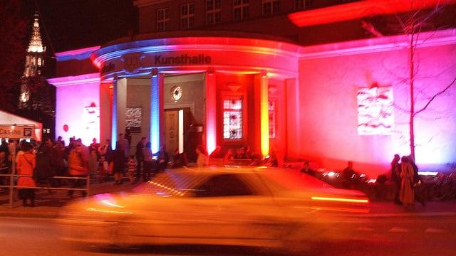 Aussenansicht der Kunsthalle Bern. Sie ist in blaues, rotes und pinkes Licht getaucht.