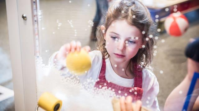 Ein Mädchen hält einen gelben Ball in der Hand und hält ihn gegen eine Scheibe.