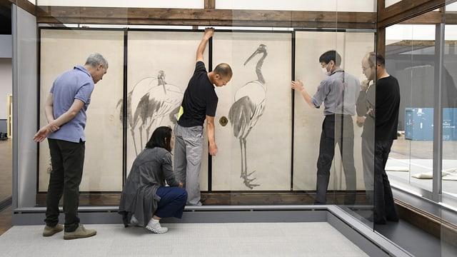 Fünf Personen bauen eine Zeichnung mit einem Vogel auf