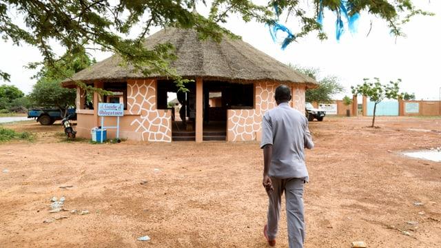 Ein Mann läuft auf das Büro des Giraffenreservates zu.