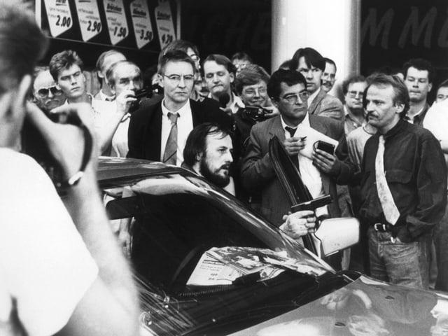 Hans-Juergen Roesner schaut aus dem Fluchtwagen und hält eine Pistole in der Hand. Um ihn herum hat sich eine Menschengruppe versammelt.