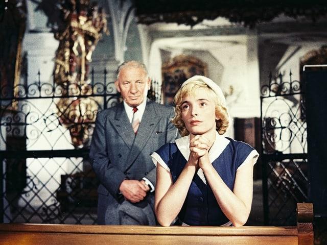 Jacqueline sitze betend in der Kirche. Hinter ihr steht ein älterer Mann, der sie betrachtet.