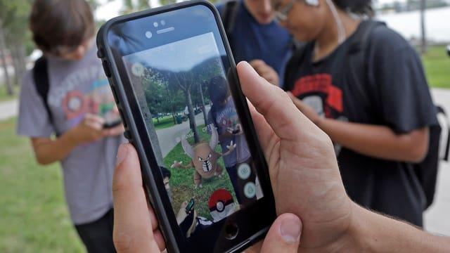 Blick auf Handybilschirm mit dem Pokemon-Spiel, im Hintergrund drei Mitspieler