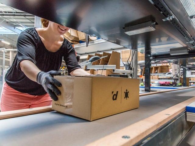 Eine Frau nimmt in einem Logistikcenter ein Paket vom Förderband