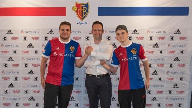 Drei Männer zum Teil im FCB Dress vor einer Werbewand.