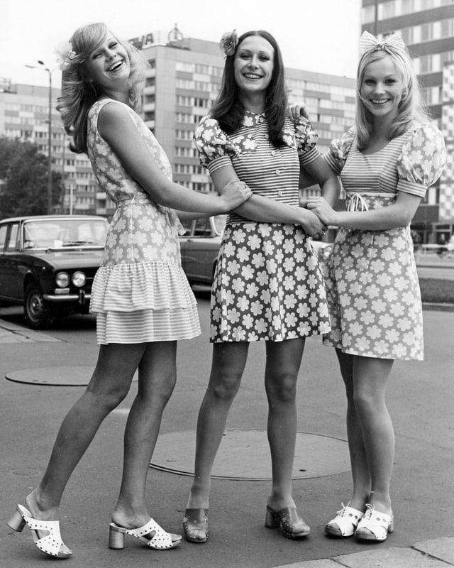 Schwarzweiss-Bild mit drei jungen Damen in blumigen Minikleidern