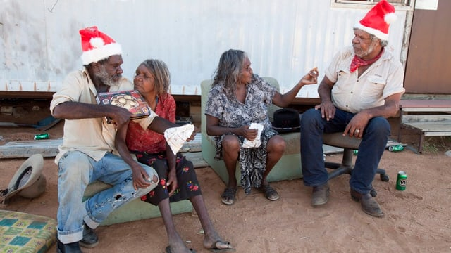 Aborigines sitzen vor ihrer Behausung.