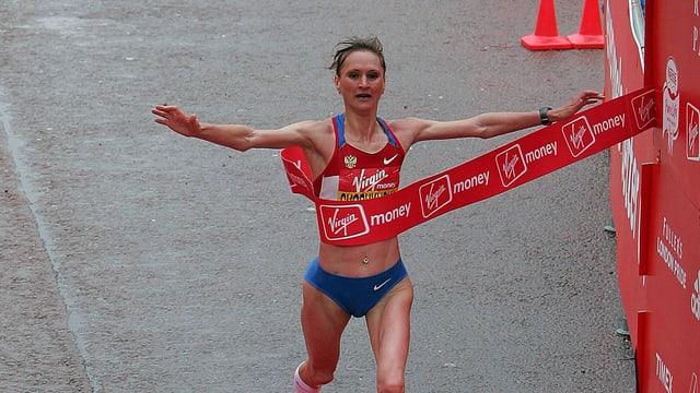 Eine Marathonläuferin durchbricht das Band im Ziel