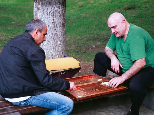Zwei Männer sitzen auf einer Bank und spielen ein Brettspiel.