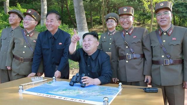 Kim sesa, ils auters sis en uniforma stattan en pe. Tuts guradan da quai cuntents.