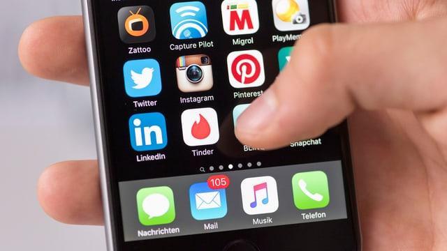 Eine Hand hält ein Smartphone mit Tinder-App.