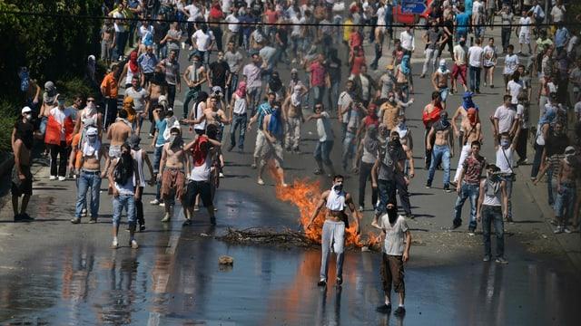 Demonstranten auf der Strasse, brennende Gegenstände.