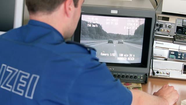 Polizist sitzt vor einem Bildschirm.
