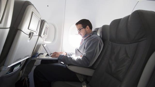 Ein Mann arbeitet im Flugzeug am Laptop.