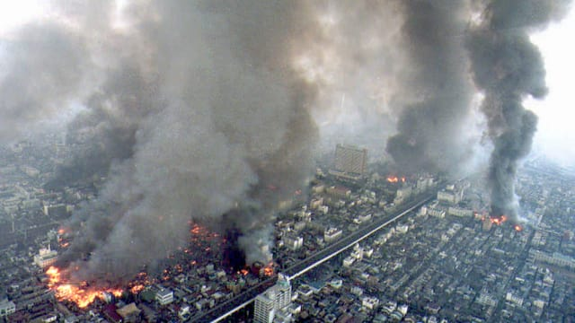 Riesige Rauchsäulen über einer Stadt.