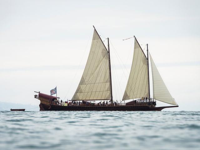 Segelschiff mit zwei Masten und drei weissen Segeln.