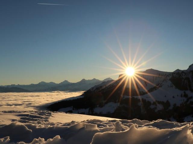 Nebelmeer mit Sonnenaufgang an Bergflanke.