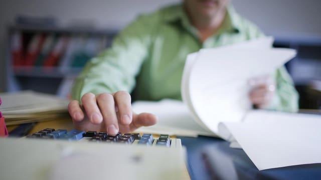 Ein Mann blättert in Unterlagen und tippt etwas in einen Taschenrechner.
