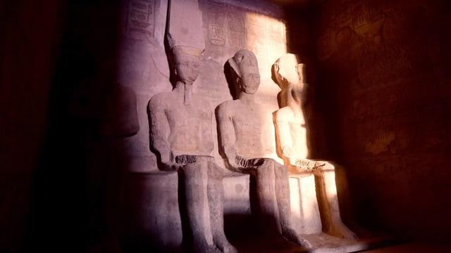 In Stein geschlagene Pharaofiguren werden von spärlichem Sonnenlicht beleuchtet