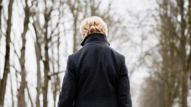 Frau von hinten in einem Wald.