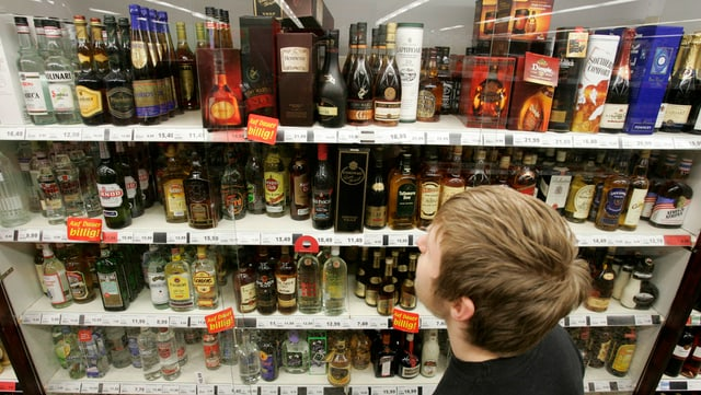 Knabe studiert Spirituosenangebot in Supermarkt.