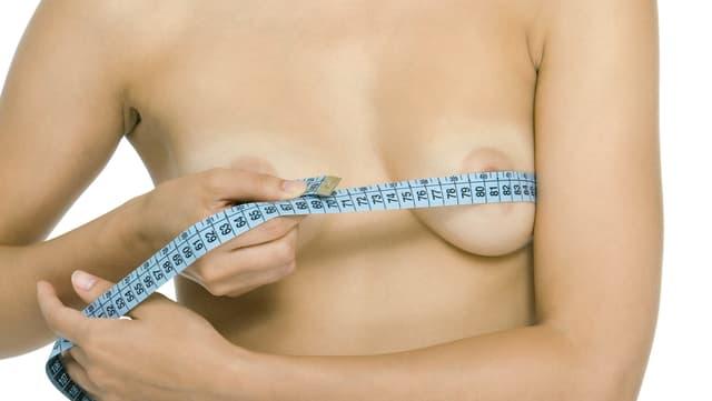 Frau mit Massband an Brust