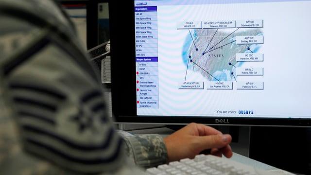 Ein Mann sitzt in Uniform an einem Computer.