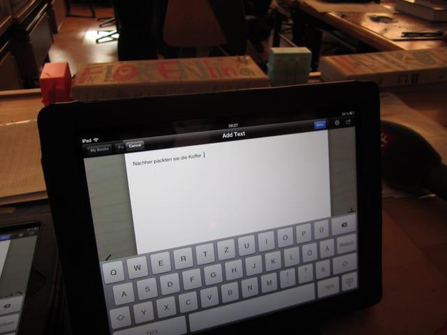 Ein schwarzes Ipad, auf dem Bildschirm die Tastatur und ein Text.