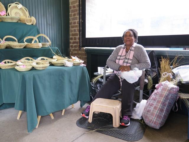 Beverly ist eine ältere schwarze Frau, die auf einem Sessel sitzt. Sie trägt ihre Haare nach hinten gekämmt und einen grauen Pulli mit pinker Schleife.