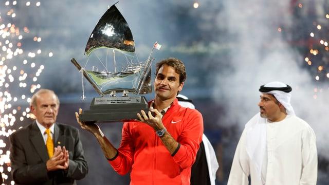 Roger Federer hält eine Trophäe in die Höhe.