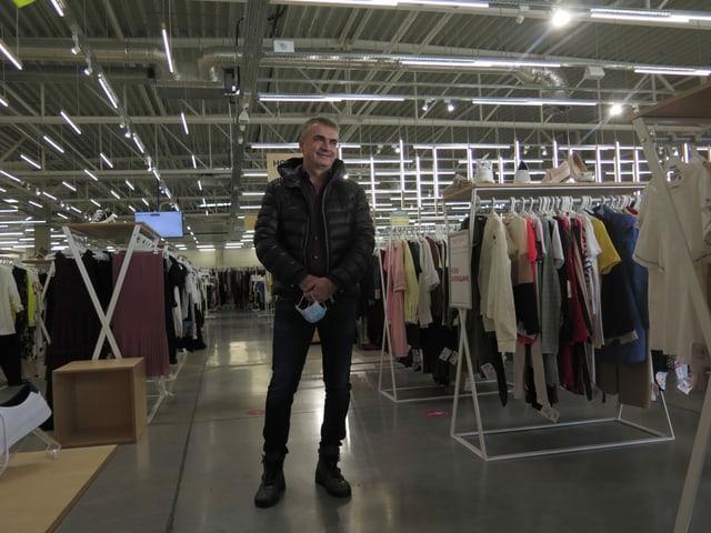 Ein Mann steht im Gang eines grossen Kleidergeschäfts und lächelt.