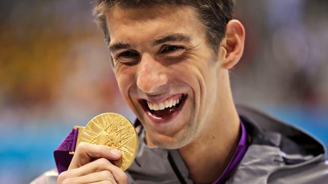 Michael Phelps lächelt und streckt eine Goldmedaille in die Kamera.